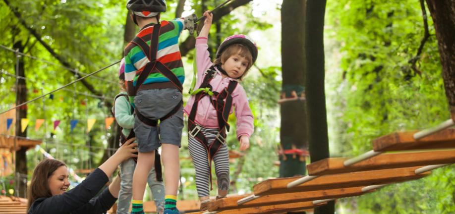 Børn leger på hængebro og får hjælp af en voksen