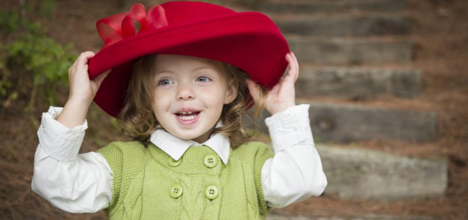 Pige i fin hat og strikket kjole
